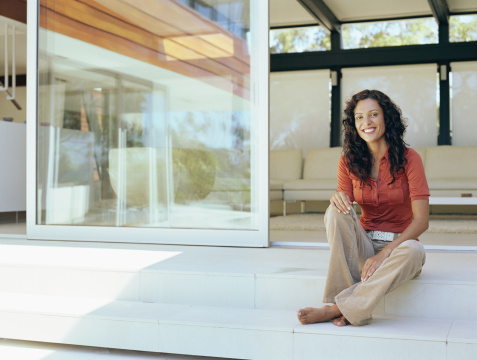 Woman Sitting On Steps By House, Smiling, Portrait
